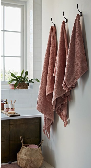Three terracotta towels handing from wall hooks in a bathroom, in front of a bathtub and woven baskets