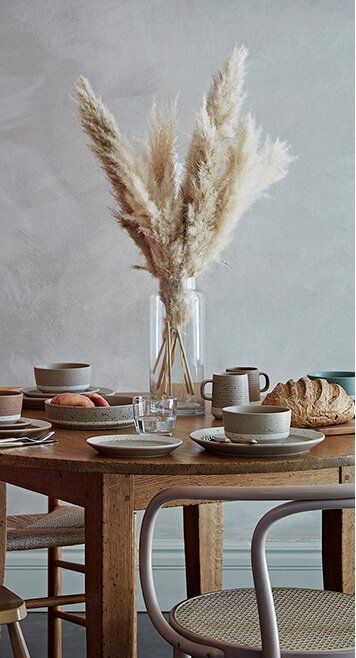 A dining table set with a selection of earthy crockery, drinking glasses, a chopping board with bread and a glass vase centerpiece filled with pampa grass
