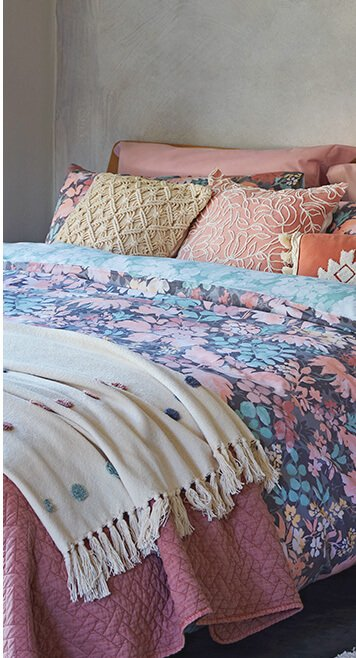 A double bed with a blue and pink floral duvet set, pink and cream accent cushions and two throws in pink and cream textured polka dots