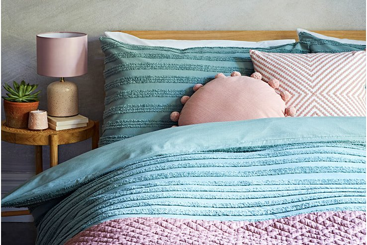 A double bed with a textured blue duvet set, a knitted purple throw and pink accent cushions next to a wooden bedside table topped with a lamp, planter and candle