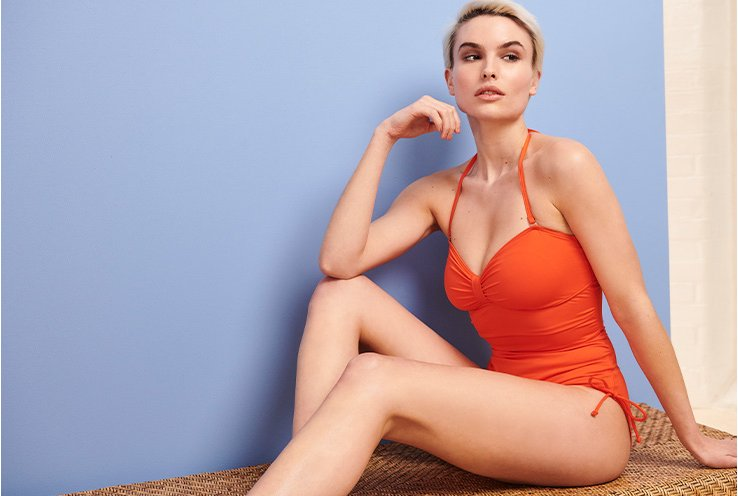 Woman wearing an orange halter neck swimsuit