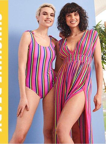 Two woman wearing pink stripe swimsuits