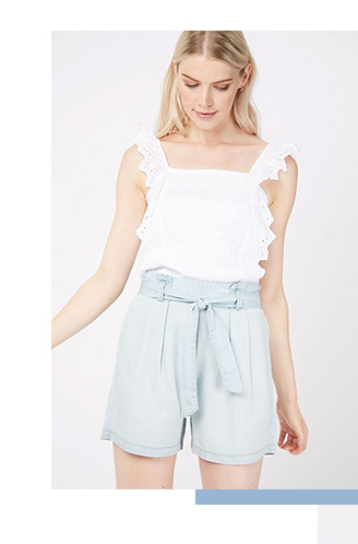 Model wearing a white broderie anglaise crop top with pale blue tie shorts