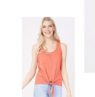 Woman wearing an orange button detail tie hem vest top and light wash jeans