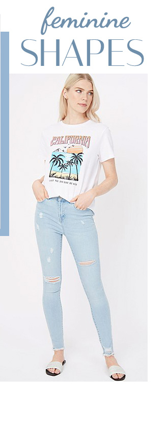Woman wearing a white California slogan t-shirt, light wash denim distressed skinny jeans and white slides