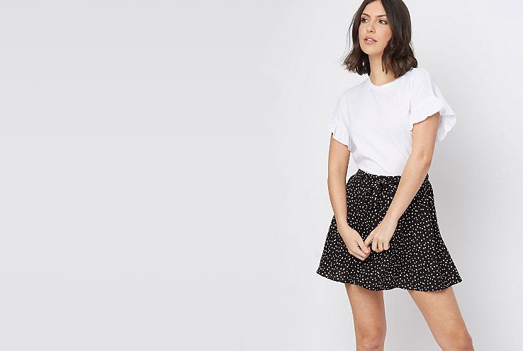 Woman wearing a white frilled sleeve t-shirt and black polka dot skirt
