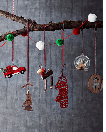 An assortment of Christmas tree decorations on a branch