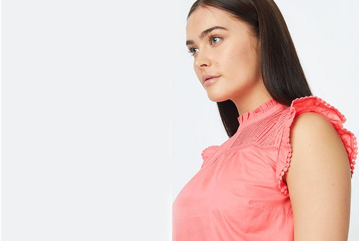 Woman with brunette hair poses side on wearing peach high neck ruffle sleeve top.