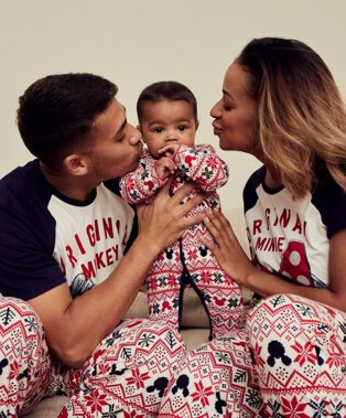 Man and woman wearing Disney Mickey Mouse matching family Christmas pyjamas lean in to kiss baby wearing matching sleepsuit.