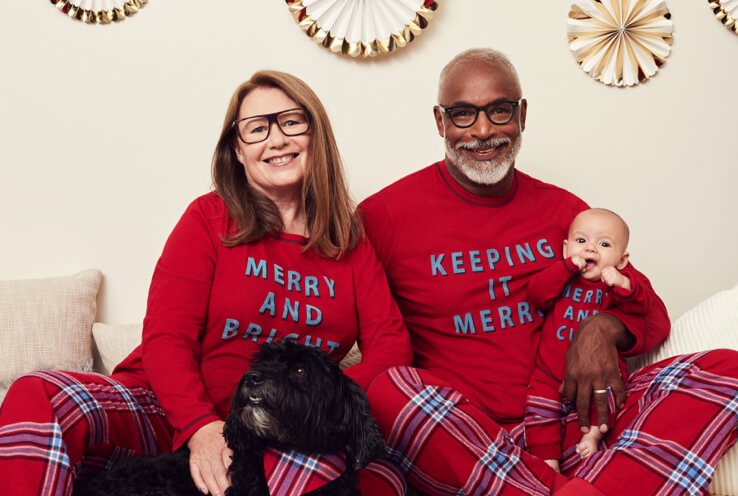 Woman, man and baby sit on huddled together on sofa wearing red 'Keeping It Merry' matching family Christmas pyjamas with gold and white decorations hanging on wall in the background.