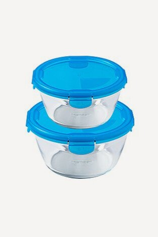 Two round pyrex storage containers with blue clip lids stacked on top of each other