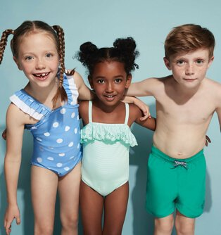 Three children standing shoulder to shoulder wearing a variety of swimming costumes and trunks