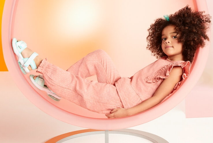 Girl poses lay side-on in pink egg chair wearing pink polka ruffle trim top, matching trousers and white sandals.