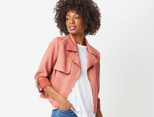 Woman wearing a pink faux suede biker jacket over a white T-shirt and jeans