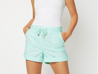 Woman wearing a white vest and turquoise shorts