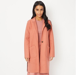 Woman wearing salmon pink longline coat over a pink top and matching skirt