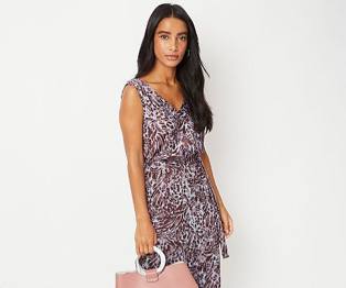 Woman wearing a patterned dress and holding a pink bag