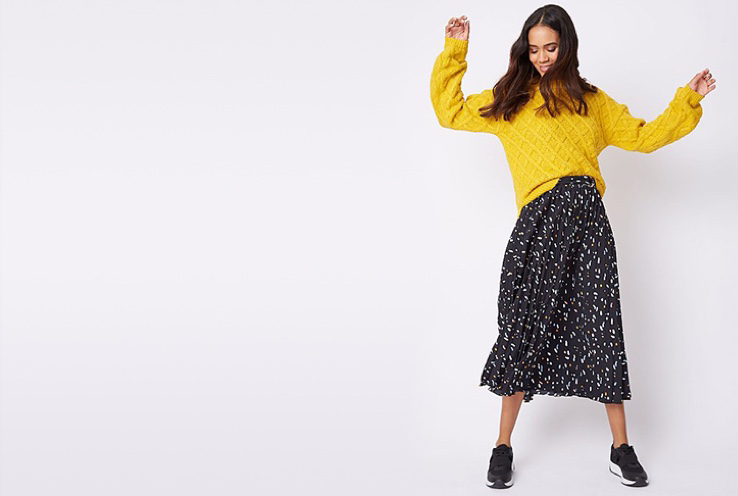 Woman wearing a yellow jumper, patterned midi skirt and black trainers