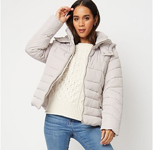 A woman wearing a cream cable knit jumper, jeans and a grey puffer jacket