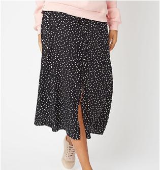 Woman wearing a black polka dot skirt and beige trainers