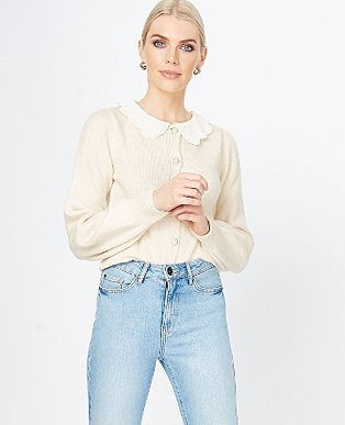 A woman wearing a cream scalloped broderie collar cardigan with blue jeans.