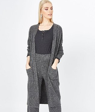 A woman wearing a charcoal open front longline cardigan over a black top, matching charcoal trousers and white trainers.