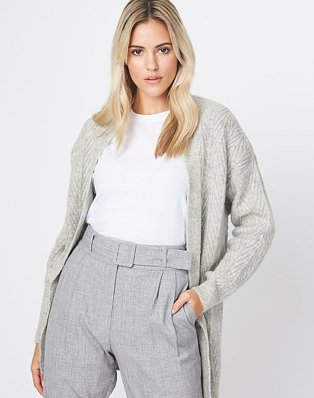 A woman wearing a grey chevron knit cardigan over a white t-shirt and grey tailored trousers.