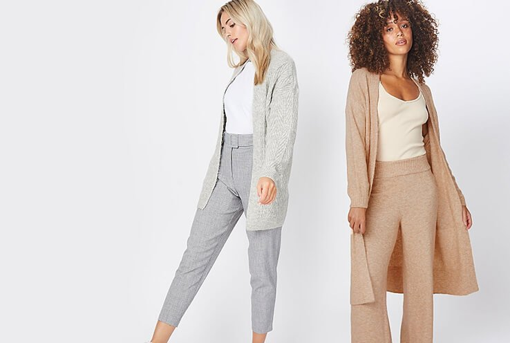 Two women wearing longline cardigans over neutral t-shirts and matching trousers, one in grey and the other in tan.