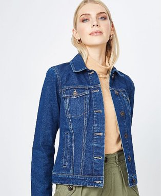 Woman poses wearing green cargo trousers, tan roll neck top and blue denim jacket.