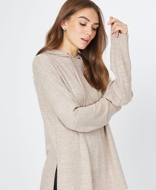 Woman poses side on resting elbow on arm wearing stone marl woven side slit hoodie.