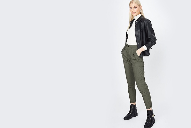 Woman poses side on wearing khaki cargo trousers, white roll neck top, denim jacket and black biker boots.