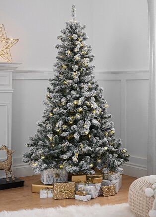 6ft pre-lit snowy pine Christmas tree with presents underneath next to white mantelpiece with gold light-up star.
