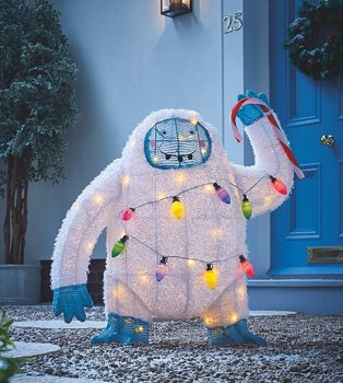 White Christmas waving Yeti light outside on grey pebbles with blue door in the background.
