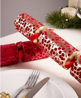 White tablecloth with metallic red and gold crackers.