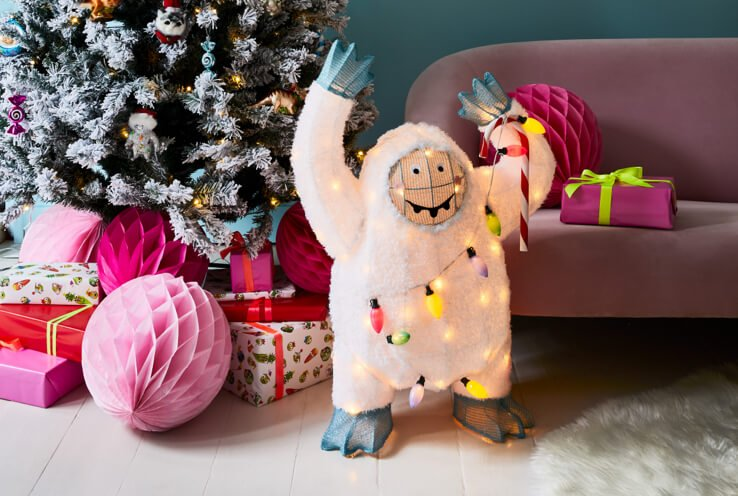 White Christmas waving Yeti light stands next to decorated Christmas tree with pink paper decorations and wrapped presents underneath with purple sofa in the background.