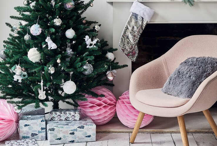 A Christmas tree decorated with silver and white baubles next to a fireplace with a silver sequin stocking and a pale pink armchair with a grey fluffy cushion.