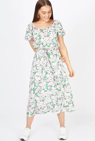 Woman poses looking down wearing green and pink floral midi dress and white trainers.