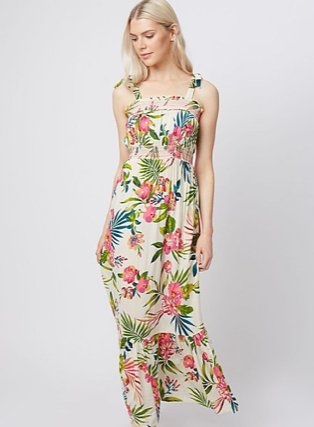 Woman poses looking down wearing multicoloured floral tiered hem midi dress.
