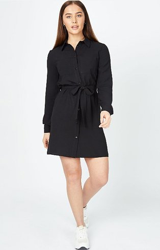 Woman poses wearing black long sleeve mini shirt dress and white trainers.