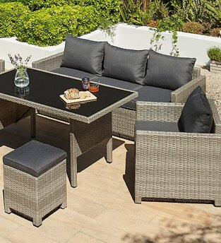 Grey rattan effect sofa and table set with black cushions, sitting on an outdoor deck