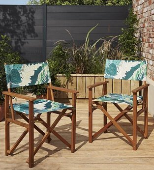 Two wooden chairs with green leaf patterned fabric