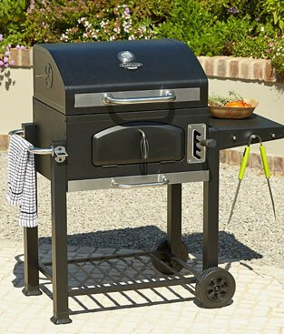 Classic amercian style charcoal grill on an outdoor patio, with tongs and a tea towel hanging on the side