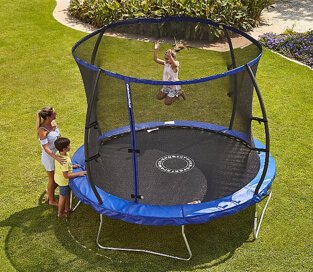 One child bouncing on a large trampoline with safety enclosure with two children watching from the side