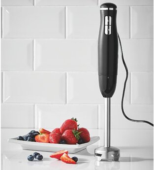 Stick blender standing upright next to a plate of berries