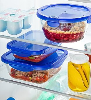 Reusable glass food containers with blue snap lids sitting on fridge shelves