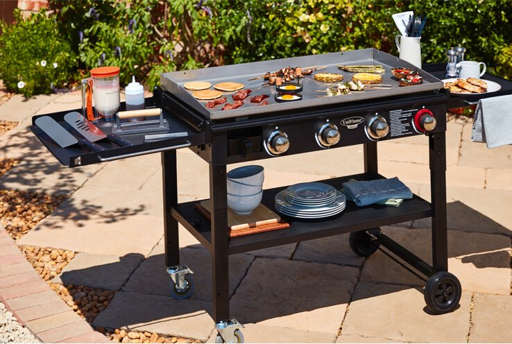 Black gas griddle cooking food on an outdoor patio