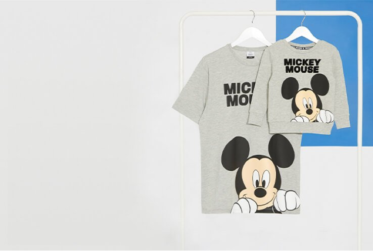 Men's grey t-shirt with Mickey Mouse on and mini Kid's jumper with Mickey Mouse on.