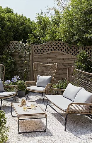 Grey wicker garden sofa set with coordinating centre table in a large garden with fence and greenery in the background.