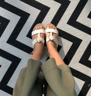 Legs of woman wearing khaki culottes and white mule sandals on white and black chevron rug.