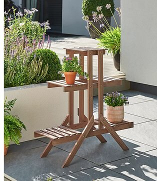 Brown wooden frame plant stand topped with plants in bright planters.